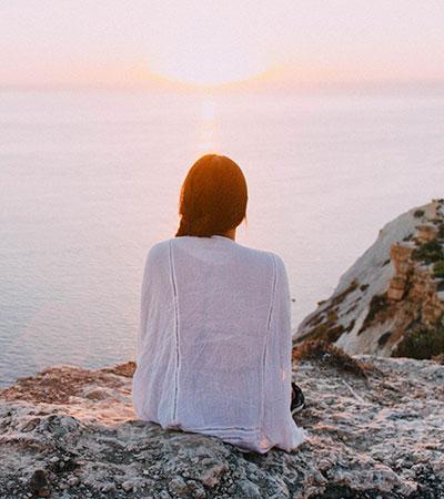 Mujer sentada en roca